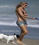 Giselle Bundchen plays on the beach with dog