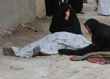 2 iraqi women look at dead us soldier under blanket