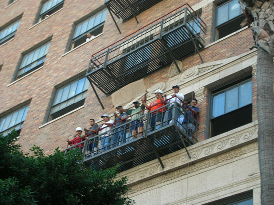 Construction workers on fire escape cheer on anti war marchers in Hollywood