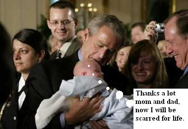 President Bush kisses a baby, parents look on