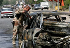 Soldier in Iraq looks at blown up car