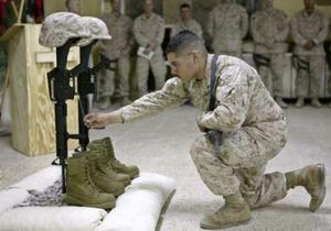 A U.S. Marine with the 3rd battalion, 1st Marine Regiment, pays his final respects during a memorial service held for Sgt. Byron W. Norwood and Lance Cpl. Abraham Simpson, at a base near the western Iraqi war-torn city of Falluja, in this handout photograph released on December 13, 2004. from 12/14/04
